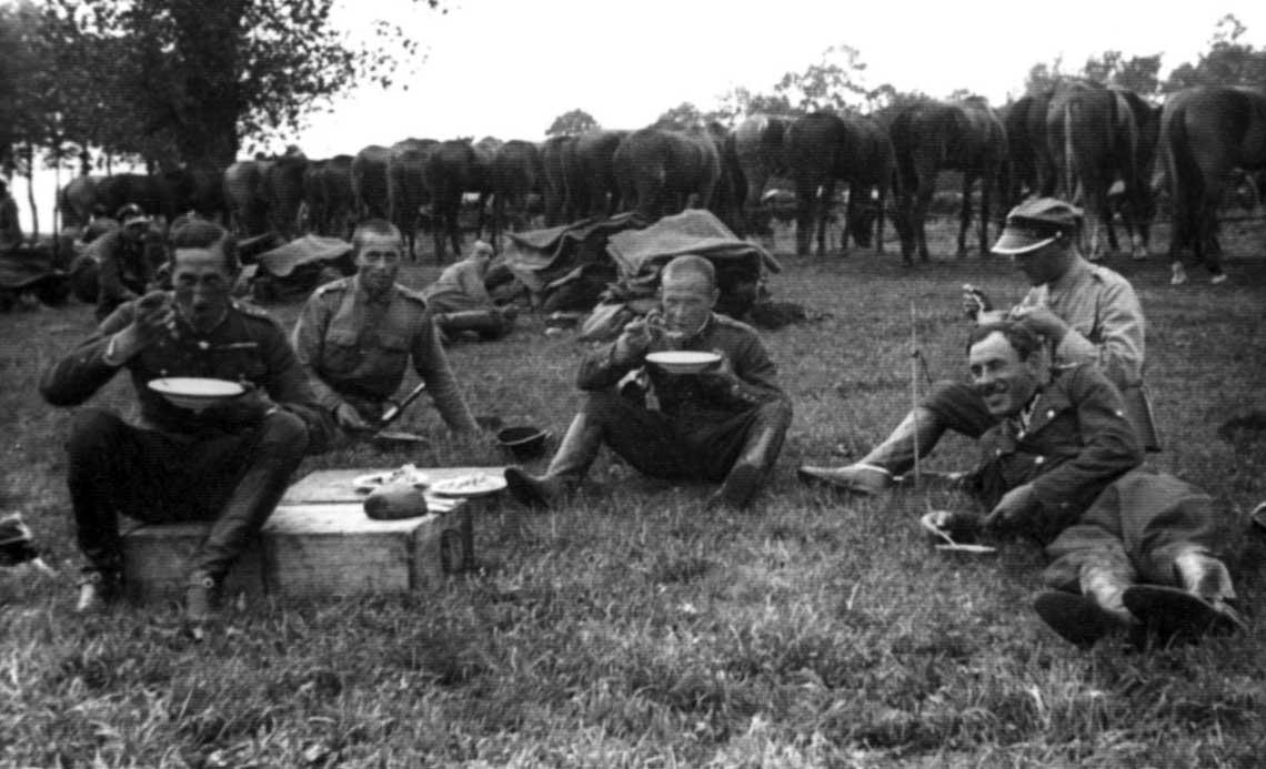 Oficerowie 4 dak z Suwałk podczas posiłku w polu; ciekawostką obok klasycznych menażek są porcelanowe talerze. Fotografia wykonana w czasie letnich ćwiczeń na poligonie w Pohulance lub Leśnej.