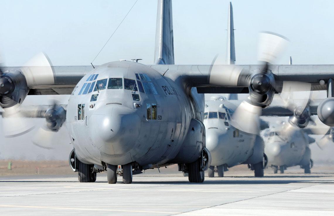 Trzy średnie samoloty transportowe C-130 Hercules kołujące do pasa powidzkiego lotniska przed startem do zawodów na celność zrzutu ładunku oraz precyzyjność lądowania.