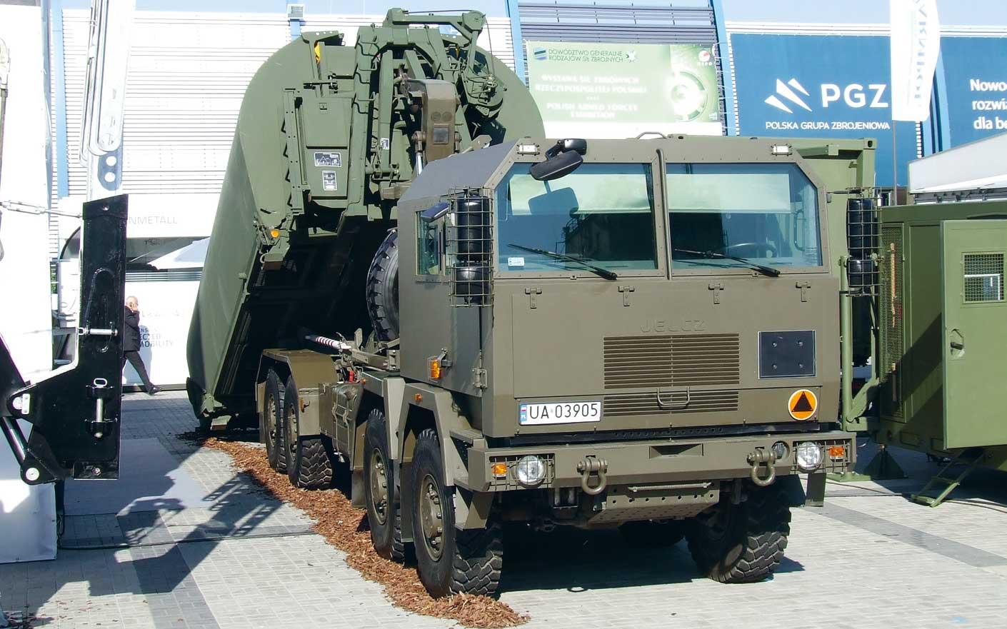Dostawy pojazdów użytkowych. Jelcz 882.53 8×8 z hakowym systemem załadowczym Multilift Mk IV i elementami składowymi mostu pontonowego IRB/PL koncernu General Dynamics European Land Systems, z platformą nośną Cargotec.