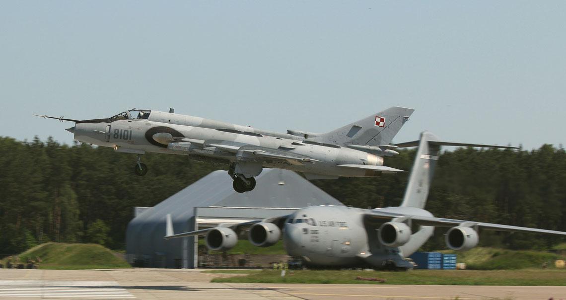 """""""Anakonda-16"""". Odrzutowe lotnictwo bojowe. Start samolotu myśliwsko-bombowego Su-22M4 na tle amerykańskiego ciężkiego transportowca C-17A Globemaster III zlotniska w Świdwinie. Fot. Cezary Adamczewski"""