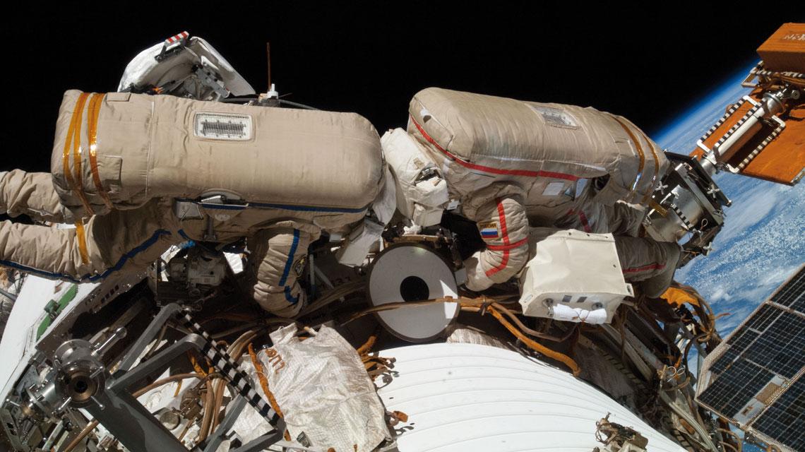 Dwójka kosmonautów w skafandrach Orłan-MK na zewnątrz ISS.