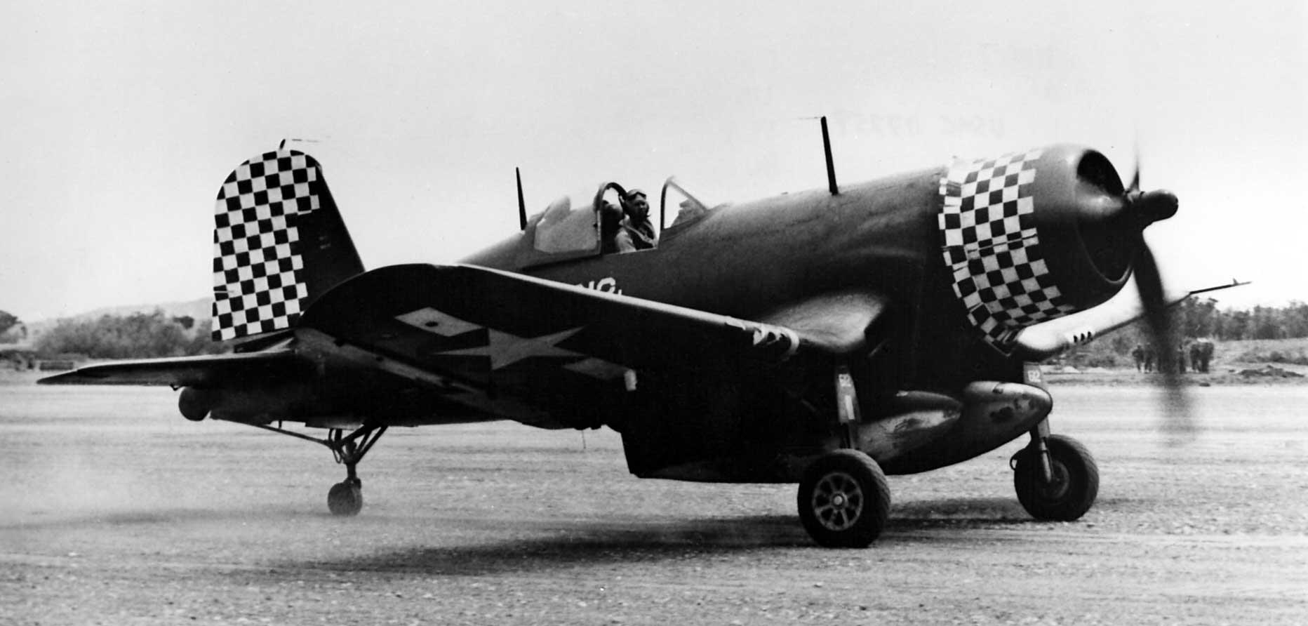 """Corsair z VMF-312 """"Checkerboards"""", noszący charakterystyczną dla tego dywizjonu szachownicę na osłonie silnika i sterze kierunku; Kadena, kwiecień 1945 r."""