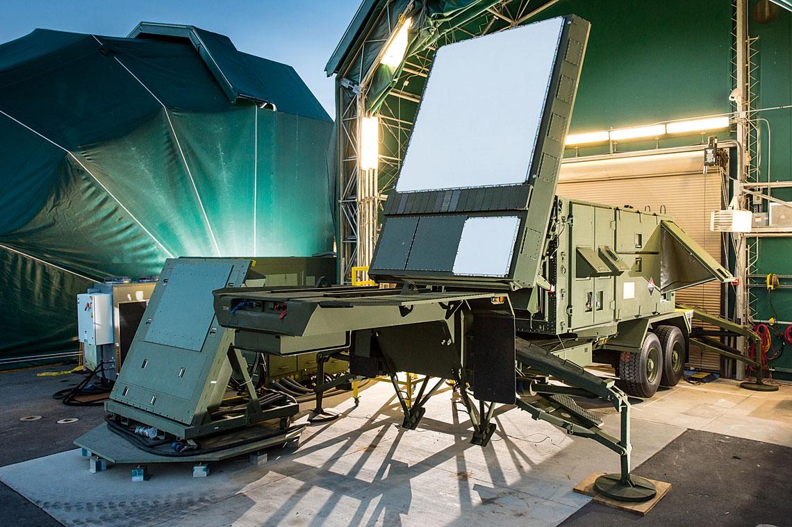 W mateczniku Patriota – wizyta w Raytheon IDS. Prototypowa stacja radiolokacyjna z AESA na bazie GaN na stanowisku w Pelham. Obok, po lewej, widać prototypową antenę boczną. Na zasłoniętym stanowisku w tle ustawiono stację AN/MPQ-65 do testów porównawczych.