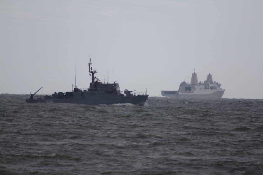 """Polski trałowiec """"wykonuje przejście w przybrzeżnej zagrodzie minowej"""". W głębi USS Arlington."""