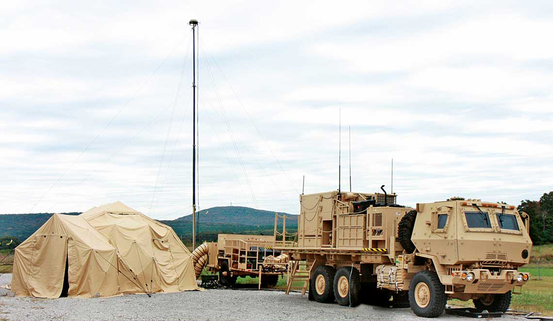 Zdjęcie z 2013 r. pokazujące pełną konfigurację bateryjnego stanowiska EOC IBCS. Po prawej serwerownia na ciężarówce M1085, po lewej namiot DRASH ze stanowiskami operatorów. Maszt systemu IFCN wydaje się być prowizorycznie dostawiony, gdyż na nowszych prototypach został zamocowany na platformie obok kontenera serwerowni.