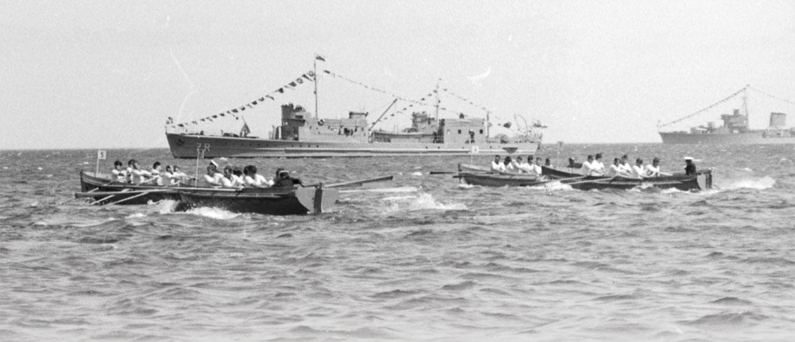1951r. – okręt hydrograficzny ORP Żuraw na redzie Gdyni. Na pierwszym planie łodzie okrętowe podczas regat wiosłowych tradycyjnie organizowanych w Dniu Marynarki Wojennej w latach 50.