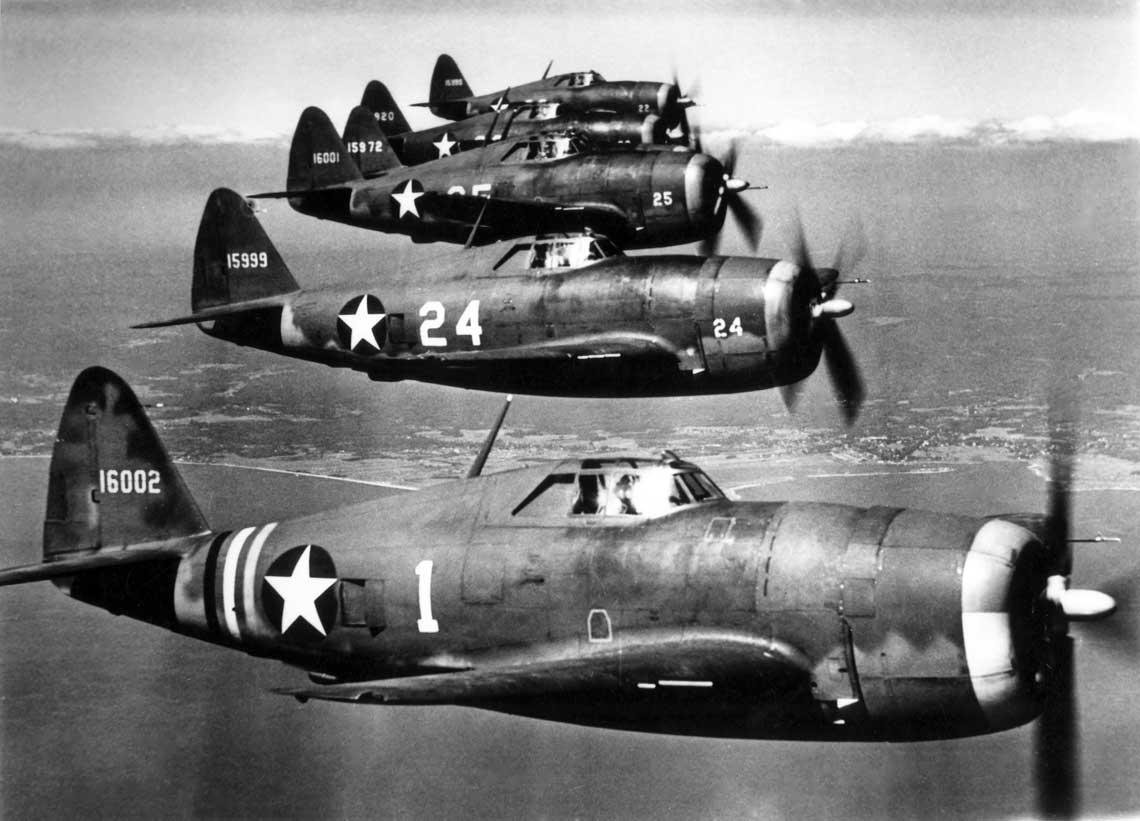 """Myśliwce P-47B z 56th Fighter Group w locie nad Long Island; lato-jesień 1942 r. Samolot na pierwszym planie (nr ser. 41-6002) pilotuje dowódca 56th FG Maj. Hubert """"Hub"""" Zemke. 56th FG była pierwszą jednostką USAAF przezbrojoną w Thunderbolty."""