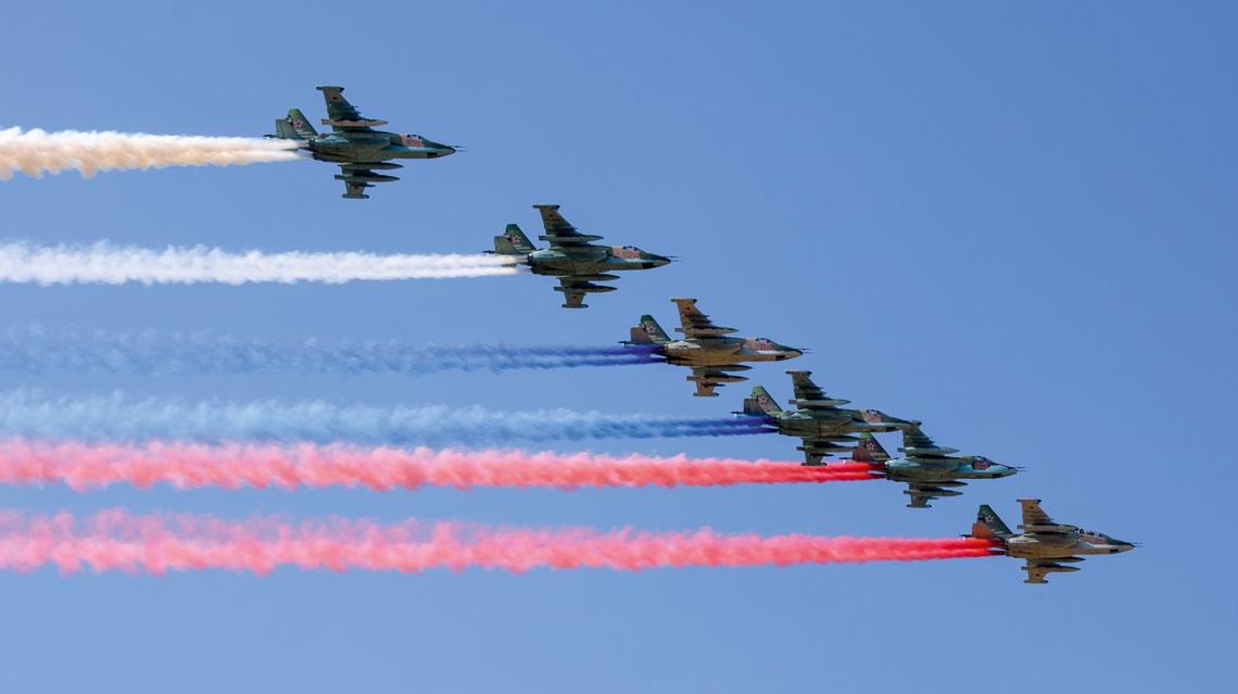 Szóstka samolotów szturmowych Su-25 z generatorami dymów w kolorach  rosyjskiej flagi – białym, niebieskim iczerwonym.