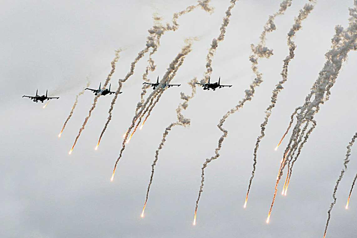 Klucz bombowców Su-34 biorących udział wćwiczeniach Zapad-2017 wefektownym ujęciu wtrakcie odpalania pułapek termicznych.
