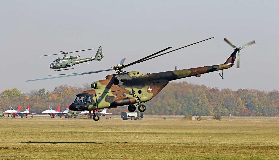 Smiglowiec transportowy HT-49/Mi-17W5 (12491) startuje po wydesantowaniu na plyte lotniska Batajnica zespolu poszukiwawczo-ratowniczego, za nim widoczny – oslaniajacy go – smiglowiec HN-45M GAMA (12918). W tle, na stojance, MiG-i-29 rosyjskiej grupy akrobacyjnej Strizi.