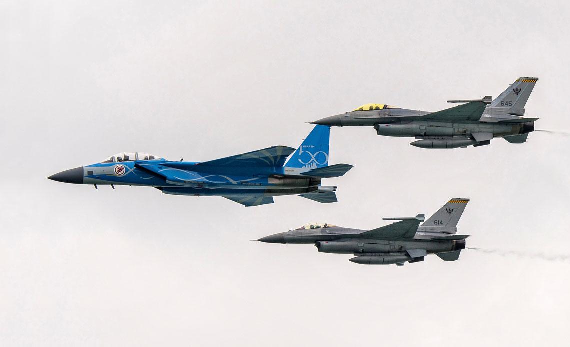 Pokazy w powietrzu otwierała trójka myśliwców Sił Powietrznych Singapuru: Boeing F-15SG w malowaniu rocznicowym i Lockheed Martin F-16C.