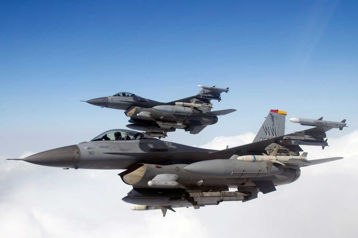 F-16CM podczas lotu treningowego. Samoloty przenosza cwiczebne wersje pociskow przeciwradiolokacyjnych AGM-88 HARM.  Na podwieszeniach podkadlubowych widac zasobniki walki radioelektronicznej AN/ALQ-184.
