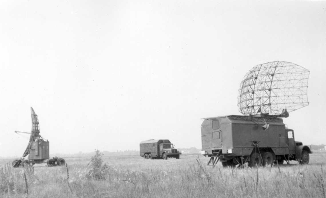 Rozstawiony w terenie polski komplet radiolokacyjny Jawor-Bogota.  Z prawej odległosciomierz Jawor, z lewej zas wysokościomierz Bogota. W srodku – samochod z kabina operatorska.