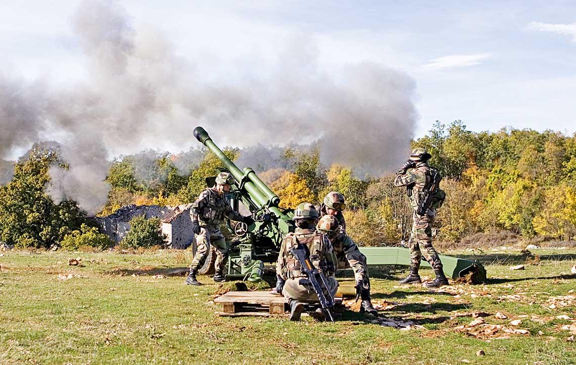Haubica Nexter Systems 105LG1 MkIII podczas pokazowego strzelania, jak widac z 5-osobowa obsluga.