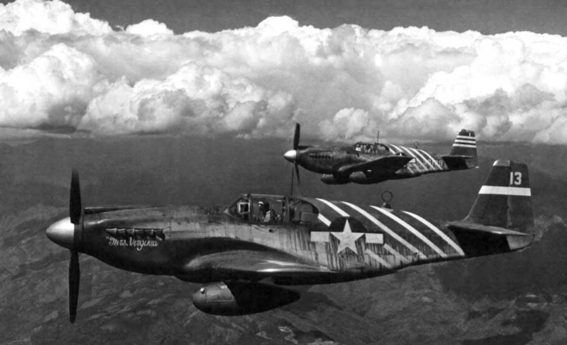 """Bodaj najslynniejsze zdjecie Mustangow (P-51A) z 1. Air Commando Group, wykonane podczas eskorty B-25 nad Birma. Na pierwszym planie """"Mrs. Virginia"""", ktorym latal Maj. Bob Petit, oficer operacyjny sekcji mysliwskiej 1. ACG; na drugim samolot dowodcy 1. ACG, Lt.Col. Philipa Cochrana. Ukosne biale pasy na kadlubie byly elementem rozpoznawczym 1. ACG."""
