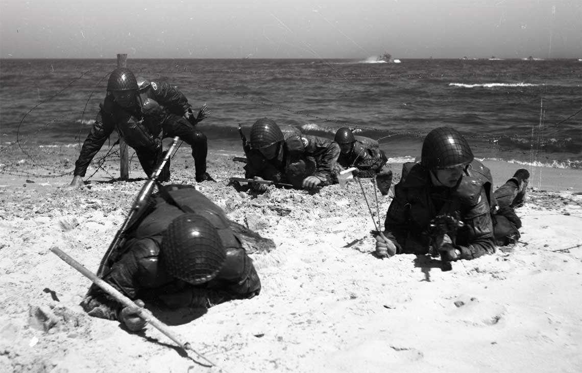 Saperzy grupy szturmowo-rozgradzajacej przygotowuja  przejscia w zaporach minowych na brzegu w walce o uchwycenie punktu ladowania desantu. Na morzu widoczne kutry desantowe projektu 709.