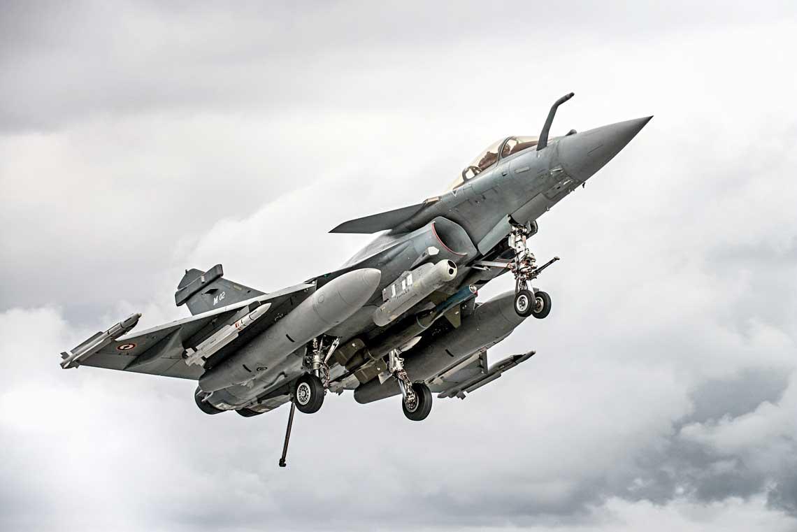 """Rafale M02 podchodzi do ladowania zpodwieszonym zasobnikiem celowniczo-nawigacyjnym Damoclès inaprowadzana laserowo bomba GBU-24 Paveway III owagomiarze 1000 kg. Samolot uzbrojony jest takze wpociski kierowane """"powietrze–powietrze"""", dwa MICA-IR i cztery MICA-EM."""
