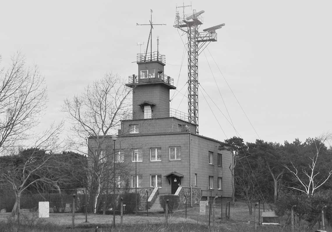 Tak w calej okazałosci prezentuje sie murowany budynek punktu  na helskim cyplu. Kilkanascie takich podobnych do siebie obiektow powstalo na przelomie lat 40. i 50. XX wieku. W drugiej polowie lat 50. dostawiono do nich kratownicowy maszt dla anten radarow. Tu na zdjeciu zamontowane dwie stacje SRN7453 Nogat.