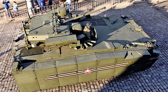 Kurganiec-25 widziany z góry. Widać siatkę na wlocie powietrza do silnika z lewej burty oraz umieszczone obok siebie włazy dowódcy i kierowcy.