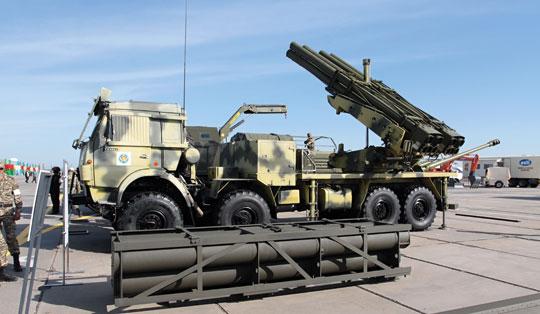 Polowy system rakietowy Naiza, czyli Lynx dla Kazachstanu na podwoziu samochodu ciężarowego Kamaz-63502. Na wyrzutni widać prowadnice pocisków kalibru 220 mm, na ziemi leży hermetyczny pakiet pocisków Extra.