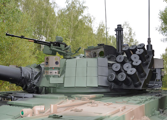 Wieża demonstratora PT-91M2 osłonięta jest modułami pancerza ERAWA. Dobrze widoczne są: zespół wyrzutni granatów dymnych, zespół czujników systemu Obra zamontowany wspólnie z głowicą systemu SOD, głowica celownika Safran SAVAN-15 i czujnik meteorologiczny.