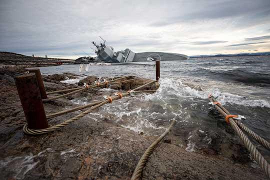 """Aby utrzymać fregatę na powierzchni, przymocowano ją do pobliskich skał. Na pierwszym planie widać stalowe liny inieprawidłowo założone zaciski na dwóch ztrzech nich (wszystkie powinny """"patrzeć"""" wjedną stronę). To właśnie ztego powodu doszło do poluzowania stalówek iopadnięcia dziobu okrętu wtoń morską."""