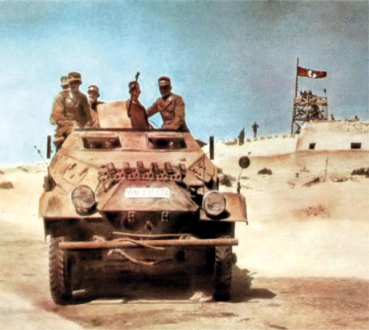 transporter dowodzenia na tle zajętego przez Niemców pustynnego posterunku Fort Mechili. Charakterystyczną cechą DAK, co najmniej do końca 1942 r., był niemal całkowity brak półgąsienicowych transporterów opancerzonych piechoty. Wozy tego typu używano wyłącznie w pododdziałach dowódczych i korygowania ognia artylerii.