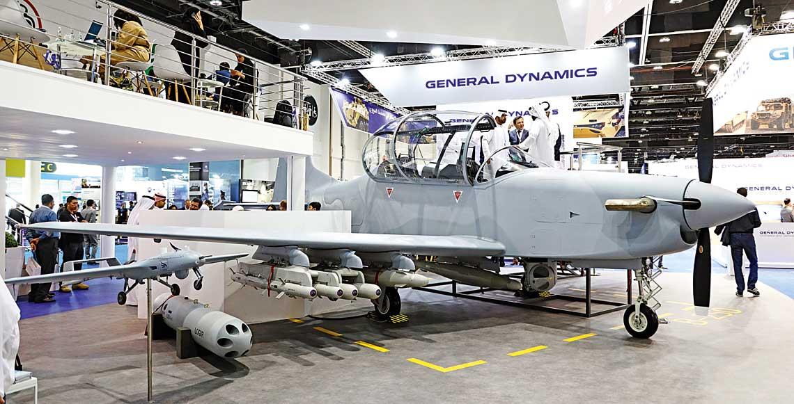 Lekki turbośmigłowy samolot szkolno-bojowy B-250 na stoisku firmy Calidus. Pod jego skrzydłami i kadłubem widoczne podwieszone pociski kierowane Desert Sting-16 i Desert Sting-35 na belkach wielozamkowych i bomby korygowane rodziny Thunder-P31/32.