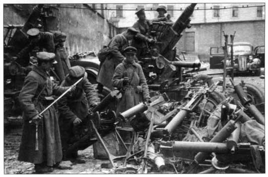 Zdobycz wojenna. Wśród wyciągniętych z magazynów antycznych ckm wz. 08 nowoczesne armaty przeciwlotnicze Bofors i szabla oficerska.