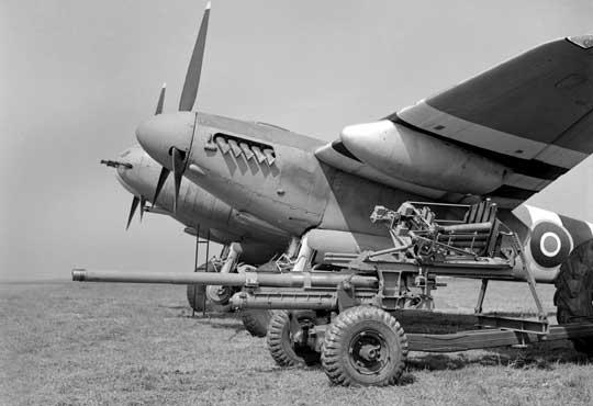 Mosquito Mk XVIII, zwany potocznie Tsetse, uzbrojony w działko kal. 57 mm (zwraca uwagę lufa wystająca w dolnej części dziobu). Na pierwszym planie, dla porównania, ta sama broń w wersji oryginalnej. Widoczny tu samolot należał do 248. Sqn RAF, azdjęcie wykonano w Portreath w Kornwalii latem 1944 r.
