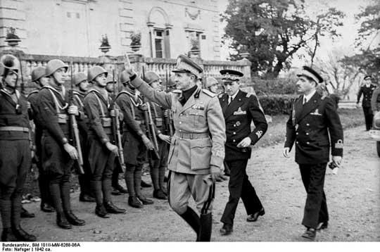 """Okupowana część Francji. Oficer """"Czarnych Koszul"""" wraz z dwoma francuskimi oficerami marynarki wizytuje kompanię piechoty morskiej."""