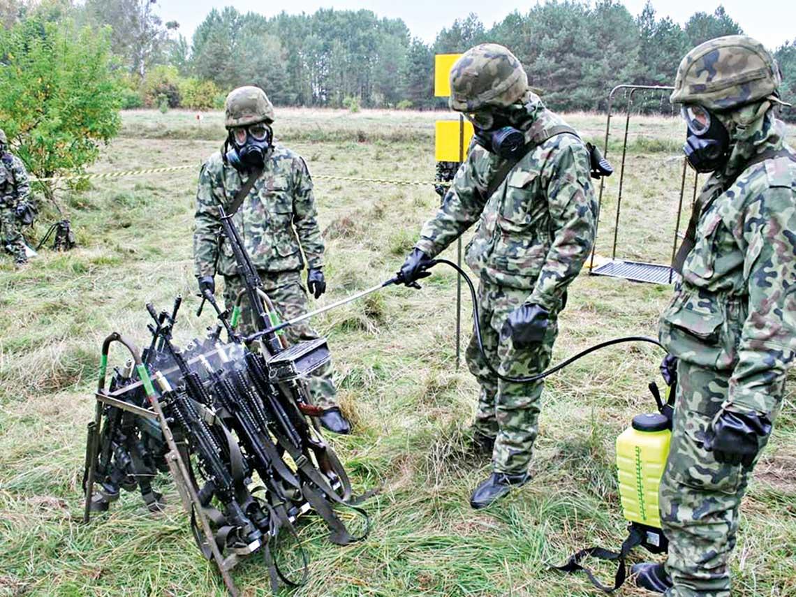 Wojskowi chemicy w odzieży FOO-1 i maskach MP-6 podczas odkażania broni strzeleckiej.