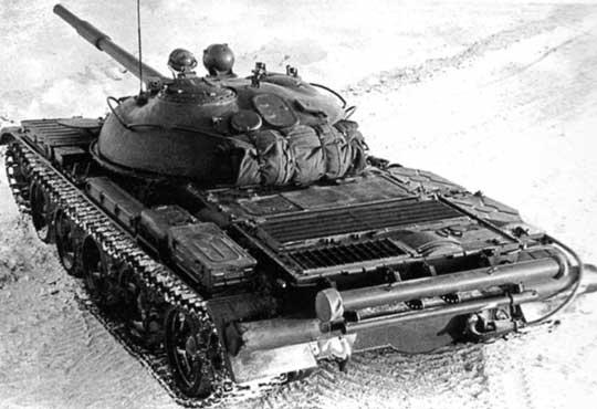Wóz dowodzenia T-62K, widoczny cylindryczny pojemnik anteny teleskopowej, zamocowany pod legarami dla beczek zpaliwem, na których leży czerpnia powietrza.