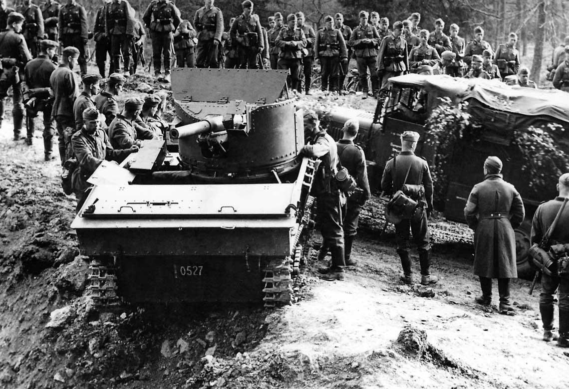 Niszczyciel czołgów T.13B2 ze złożonym pancerzem i armatą skierowaną w kierunku do przodu. Porzucony wóz oglądają niemieccy żołnierze; maj 1940 r.