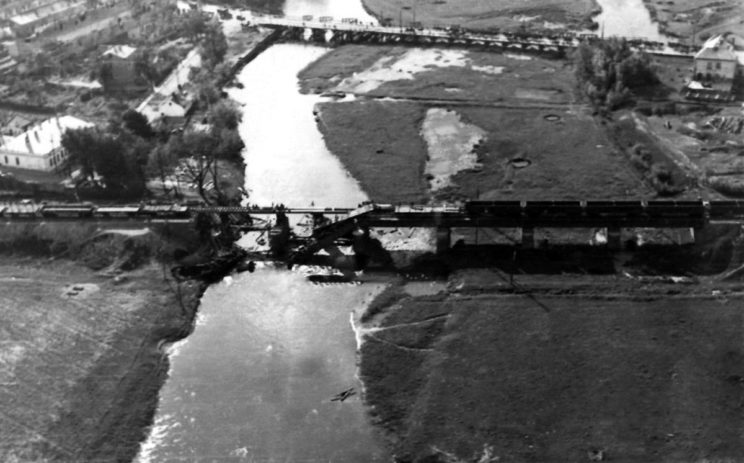 Zniszczony most kolejowy w Łowiczu w trakcie odbudowy. Wycofujące się Wojsko Polskie zniszczyło za sobą niektóre mosty na Bzurze, w tym most drogowy i kolejowy w Łowiczu (w tle, prowizorycznie odbudowany).
