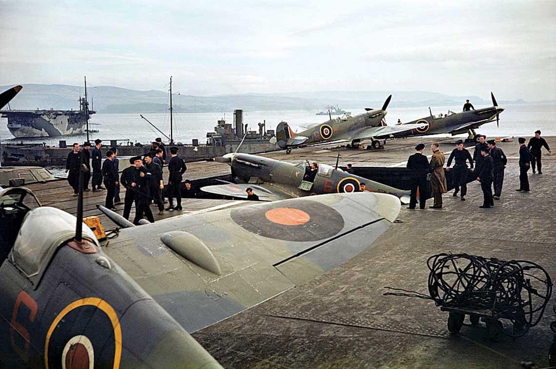 """Samoloty 899. NAS na pokładzie HMS Indomitable, szykowane do operacji """"Husky""""; Scapa Flow, czerwiec 1943 r. Zwraca uwagę poszerzona winda, dzięki której okręt mógł zabierać pod pokład samoloty z nieskładanymi skrzydłami."""
