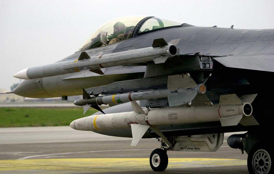 """Samolot myśliwski F-16C uzbrojony wkierowane pociski rakietowe """"powietrze-powietrze"""" średniego zasięgu AIM-120C AMRAAM (na końcówce skrzydła) oraz małego zasięgu AIM-9X Sidewinder."""