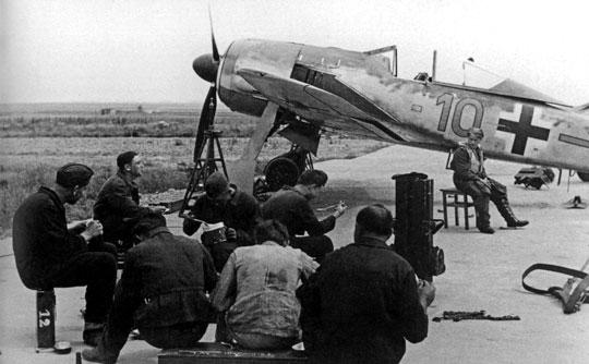 """Personel 6./JG 26 podczas pogotowia bojowego, w tle Fw 190 A-1, """"brązowa 10""""."""