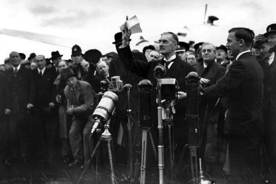 """Premier Wielkiej Brytanii, Neville Chamberlain, przemawia na lotnisku Heston, po powrocie z konferencji w Monachium. Wbrew legendzie zdawał sobie sprawę, że porozumienie nie oznacza """"pokoju na miarę czasów""""."""