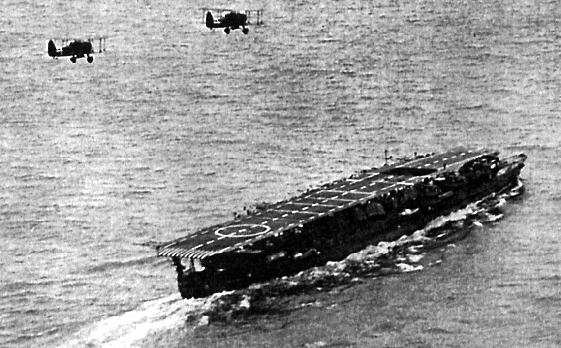 Lotniskowiec lekki Ryūjō oraz bombowiec nurkujący Typ 94 (Aichi D1A2, nazwa kodowa – Susie). Zdjęcie zostało wykonane w1938r., prawdopodobnie podczas działań naMorzu Południowochińskim. Ryūjō był jednym zestarszych lotniskowców japońskiej marynarki wojennej. Jego grupa lotnicza liczyła do34operacyjnych samolotów (w zależności odokresu), załogi zaś posiadały duże doświadczenie bojowe. Lotniskowiec brał udział w wojnie japońsko-chińskiej, a także dwa miesiące wcześniej stanowił trzon sił uderzeniowych zespołu wiceadmirała Jinsaburō Ozawy podczas rajdu nabrytyjskie linie zaopatrzeniowe w Zatoce Bengalskiej.