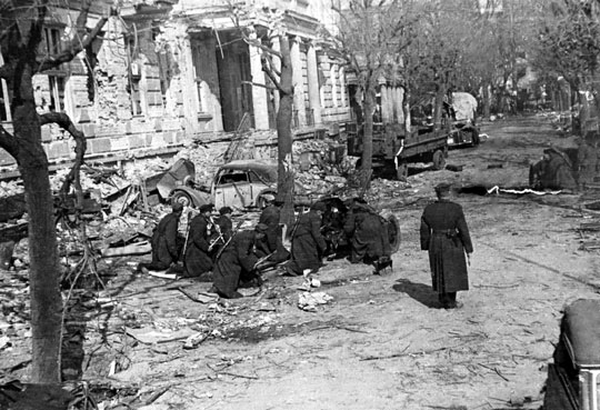Armata przeciwpancerna 45 mm podczas walk o Kołobrzeg, marzec 1945 r. Armaty tego kalibru stanowiły podstawową broń przeciwpancerną batalionów WP (po jednym plutonie). Prezentowana fotografia prawdopodobnie była pozowana – oficer stojący na środku ulicy nie miał szans na przeżycie podczas walk.