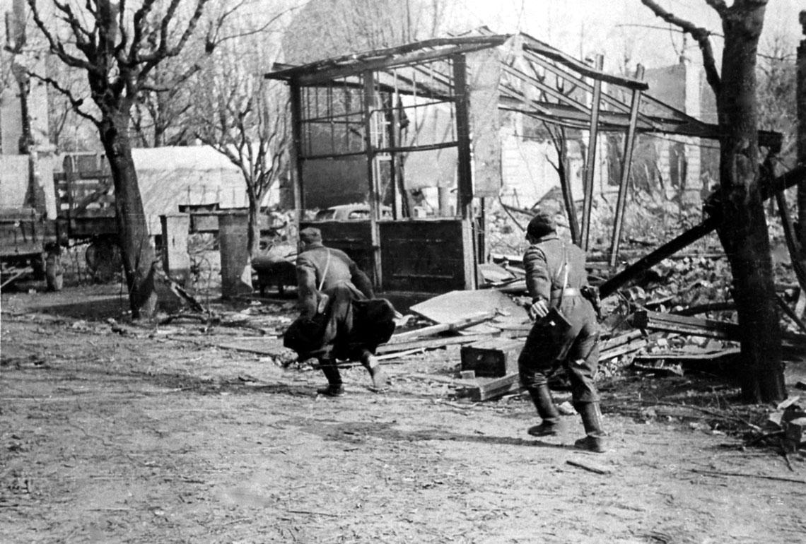 Polscy żołnierze przekraczają ulicę pod ogniem niemieckim podczas walk o Kołobrzeg w marcu 1945r. Warto zwrócić uwagę na drugiego zbiegnących – ubrany jest w kombinezon wojsk pancernych, wydawany w WP m.in. żołnierzom samodzielnych dywizjonów artylerii pancernej, będących jednostkami organicznymi dywizji piechoty.