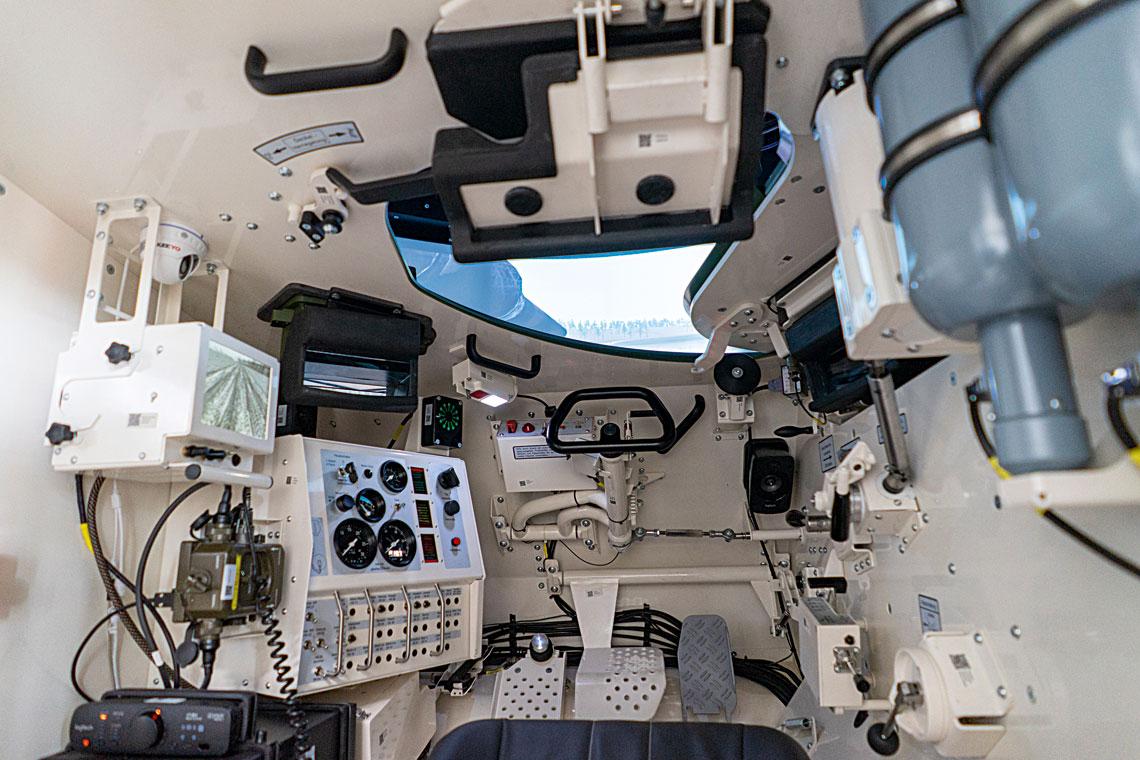 Wnętrze kabiny symulatora – dobrze widoczne jest realistyczne odwzorowanie środowiska pracy kierowcy czołgu. Wlewym rogu widoczny monitor kamery cofania, pozwalający szkolić także kierowców wozów wersji A5, anad nim kamera umożliwiająca śledzenie pracy szkolonego żołnierza.