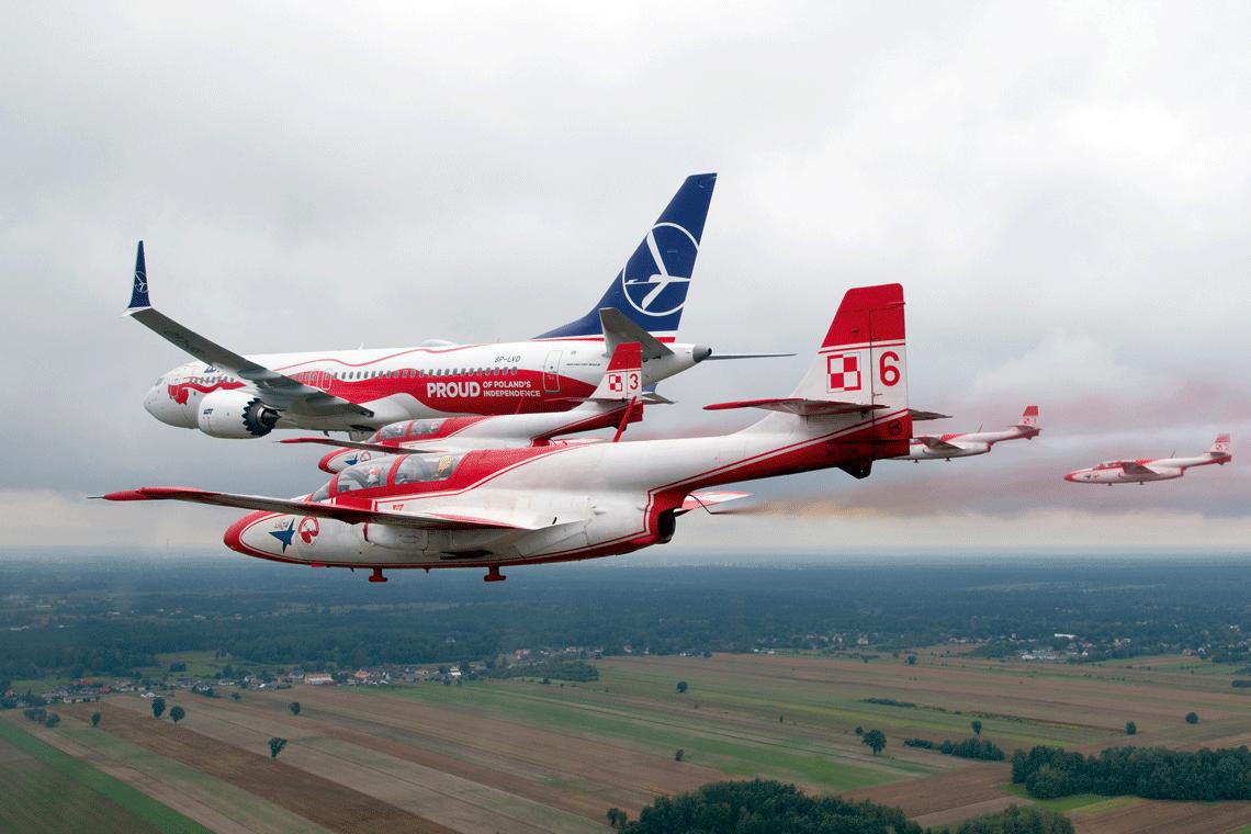 """Jeden z B737 MAX PLL LOT otrzymał okolicznościowe malowanie z okazji stulecia odzyskania przez Polskę niepodległości. Na zdjęciu samolot wszyku z TS-11 Iskra zespołu """"Biało-Czerwone Iskry""""."""
