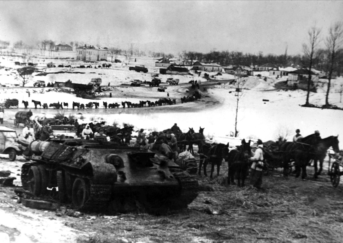 Niemieckie wojska przechodzą obok zniszczonego sowieckiego czołgu T-34; wieś Brickoje, rejon lipowiecki, obwód winnicki, styczeń 1944 r.