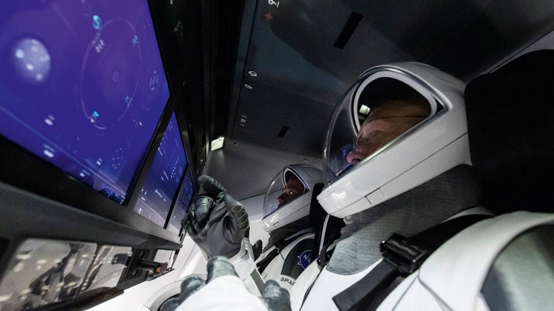 Załoga w kabinie statku kosmicznego SpaceX Dragon przed startem.