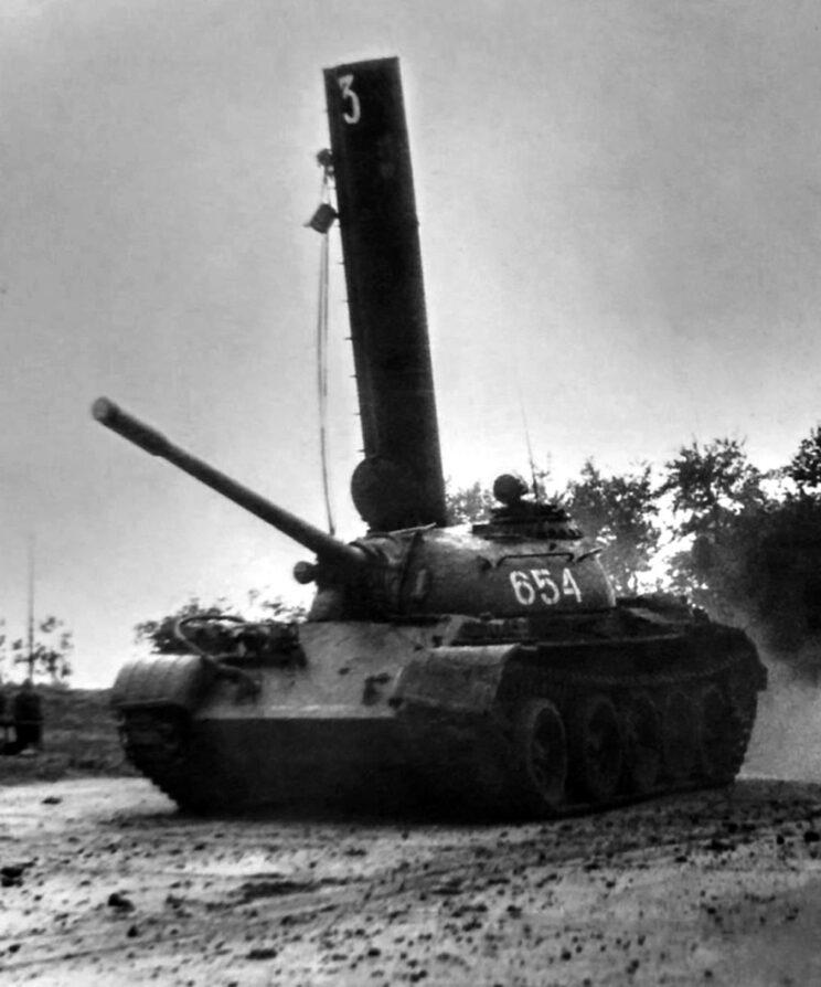 Czołg T-55 ze szkolną czerpnią powietrza na włazie dowódcy szykuje się do forsowania przeszkody wodnej.