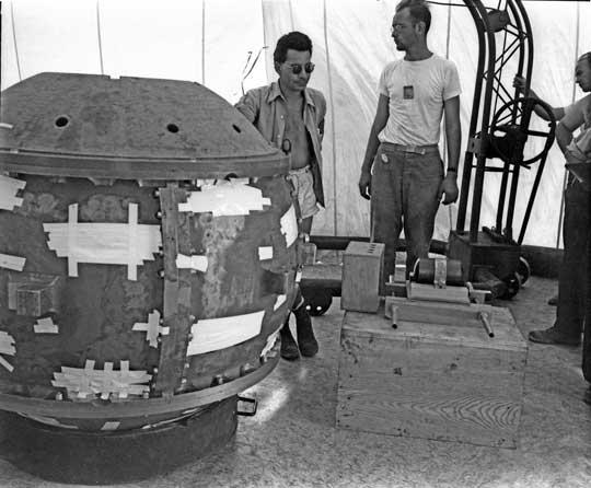 Korpus Gadgeta w namiocie u podstawy wieży w trakcie przygotowania do testu. Wszystkie otwory w korpusie zabezpieczono taśmą samoprzylepną. Zamiast górnej kopuły korpusu zamontowana pokrywa technologiczna z otworem, umożliwiająca włożenie uranowej zatyczki z rdzeniem plutonowym. Zatyczka z rdzeniem to metalowy, cylindryczny przedmiot, zabezpieczony opaską, leżący na drewnianej skrzynce po prawej.