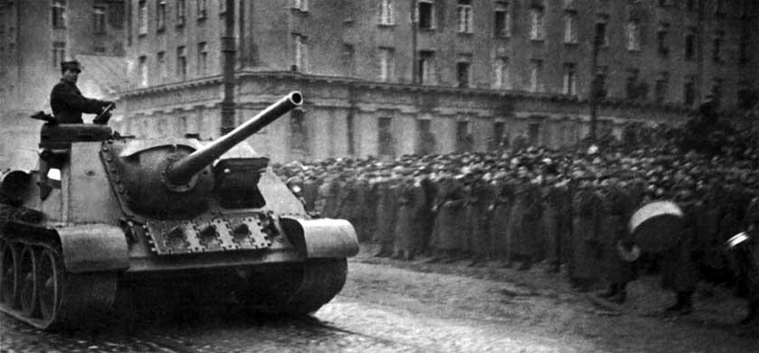 """Działo samobieżne SU-85 z 13 pułku artylerii samobieżnej z 1 Armii WP w czasie defilady na ulicach Pragi w listopadzie 1944 r. Pojazd pomalowany jednolicie w kolorze ciemnozielonym, zwraca uwagę brak numerów taktycznych i godeł na pancerzu. Cztery działa SU-85 z 13 pas brały udział w polskiej """"odpowiedzi"""" na niemiecki kontratak z 27 października 1944 r. pod Buchnikiem."""