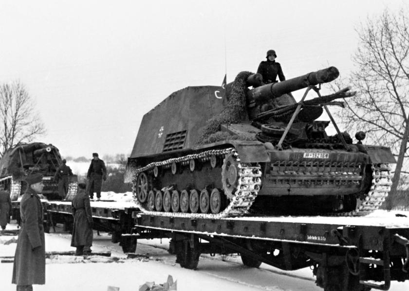 """Działa samobieżne Hummel załadowane naplatformy kolejowe, należące do 9. Pułku Artylerii SS z9.DPanc SS """"Hohenstaufen"""". Był to jeden zpodstawowych wozów bojowych zbudowanych napodwoziu PzKpfw IV, choć miało ono także elementy PzKpfw III, np. skrzynię biegów."""